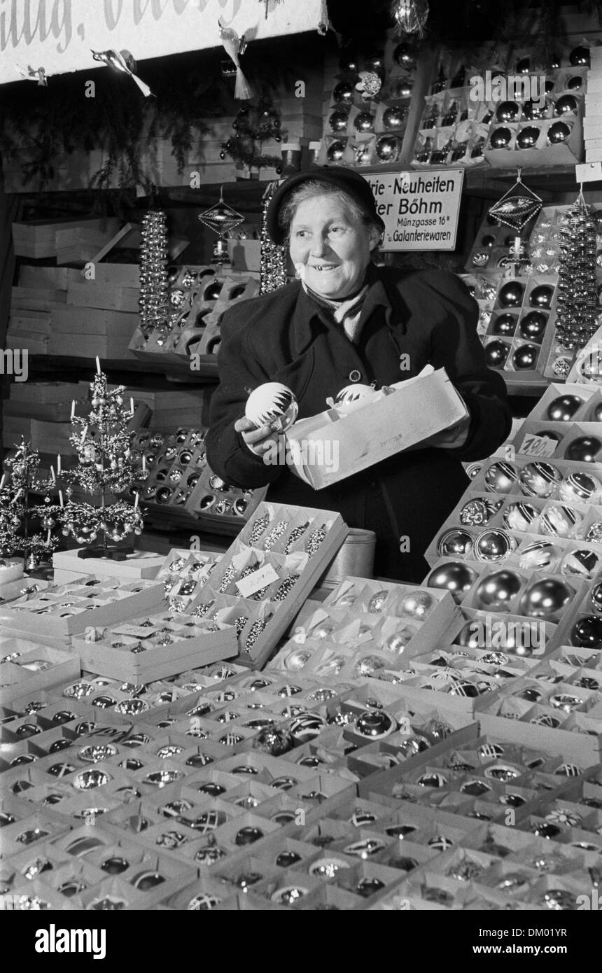 A vendor shows Christmas tree decorations at a stall on the Christmas market in Leipzig, Germany, undated photograph (1955). Photo: Deutsche Fotothek/Rössing - Stock Image