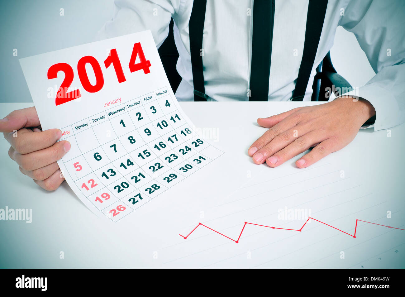 businessman sitting in a desk with a chart and showing a 2014 calendar Stock Photo