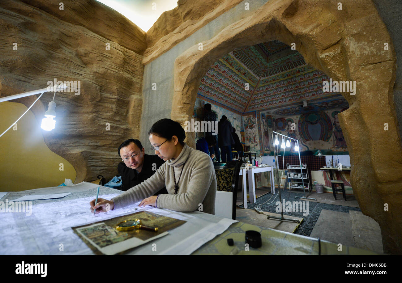 (131210) -- XI'AN, Dec. 10, 2013 (Xinhua) -- Yang Dongmiao (R) and her husband Jin Weidong draw a draft in front of the restored No. 220 grotto of Mogao Grottoes in Xi'an, capital of northwest China's Shaanxi Province, Dec. 10, 2013. Yang Dongmiao and her husband Jin Weidong, as well as their four students, have been reproducing the complete murals of the No. 45 and No. 220 grottoes of the Mogao Grottoes, a UNESCO world heritage in northwest China's Gansu Province, for almost two years. As a great number of original murals were severely damaged, they had to fill in new paintings after thoroug - Stock Image