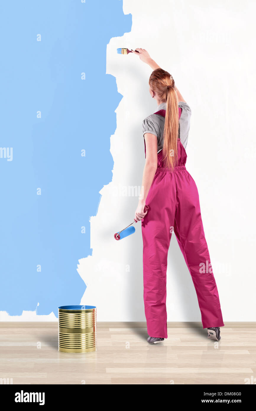 Young woman in red overalls with painting tools - Stock Image