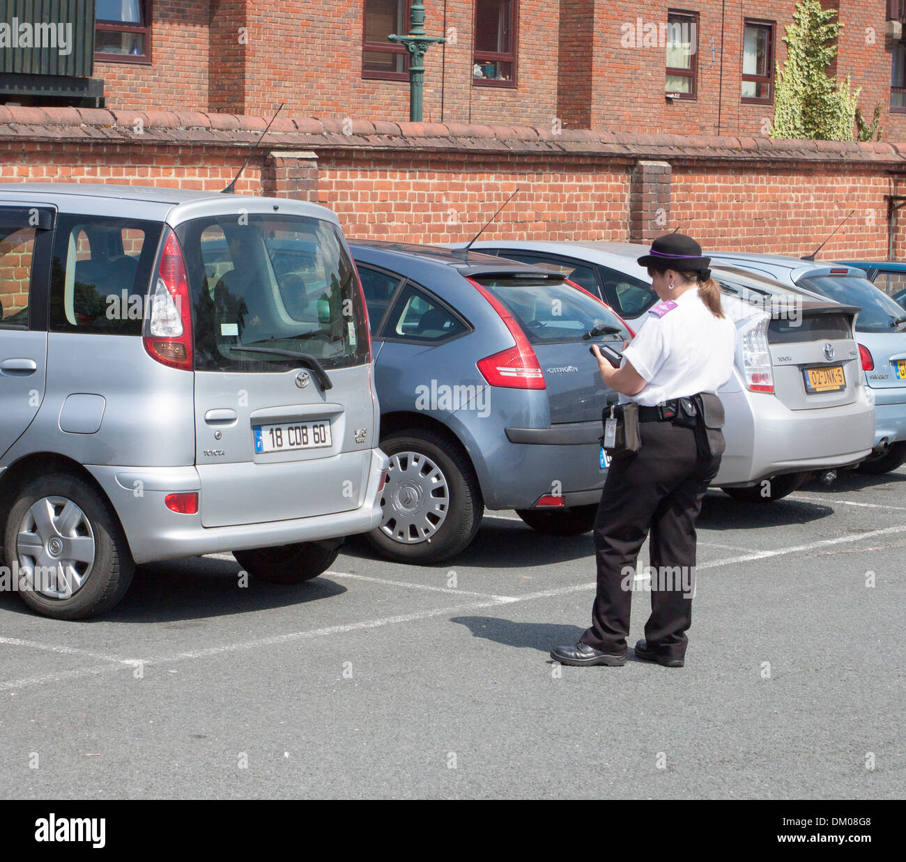 Traffic Warden issuing a parking ticket to foreign visitors car in Canterbury England - Stock Image