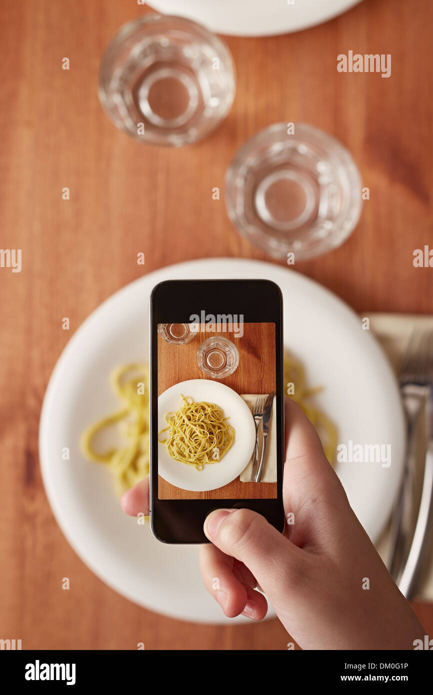 Hands taking photo of Italian pasta lunch with smartphone - Stock Image