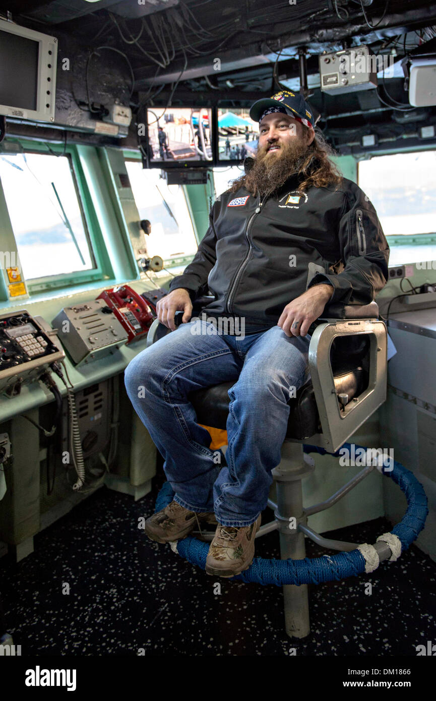 Duck Dynasty reality television star Willie Robertson sits in the commanding officer's chair during a tour of the bridge aboard the Arleigh Burke-class guided-missile destroyer USS Stout December 7, 2013 in Souda Bay, Greece. Robertson's visit is part of the annual USO holiday tour to help boost the moral of service members deployed overseas. - Stock Image