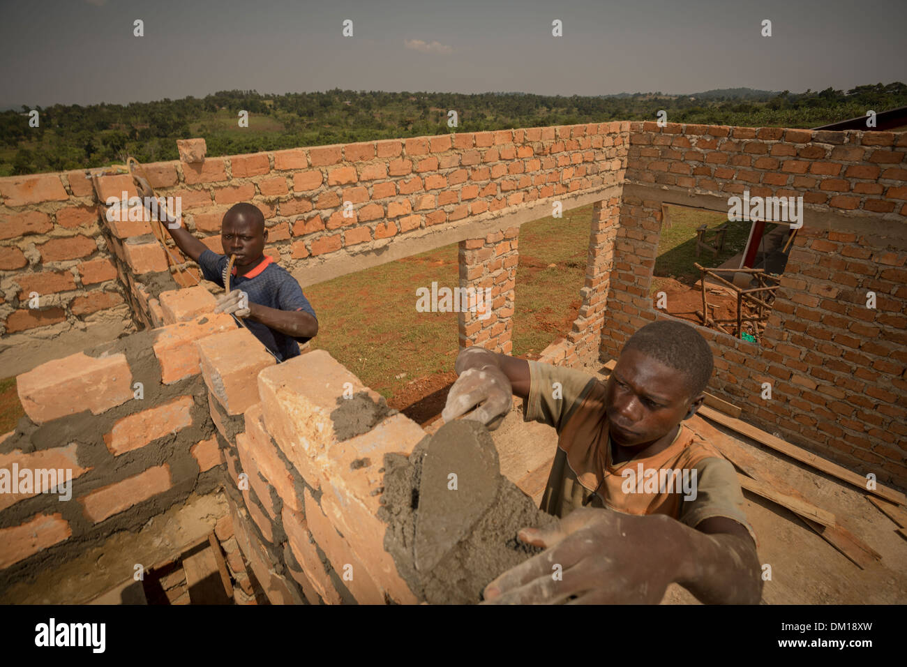 Construction workers build a new warehouse on the outskirts of Kampala, Uganda, East Africa. Stock Photo