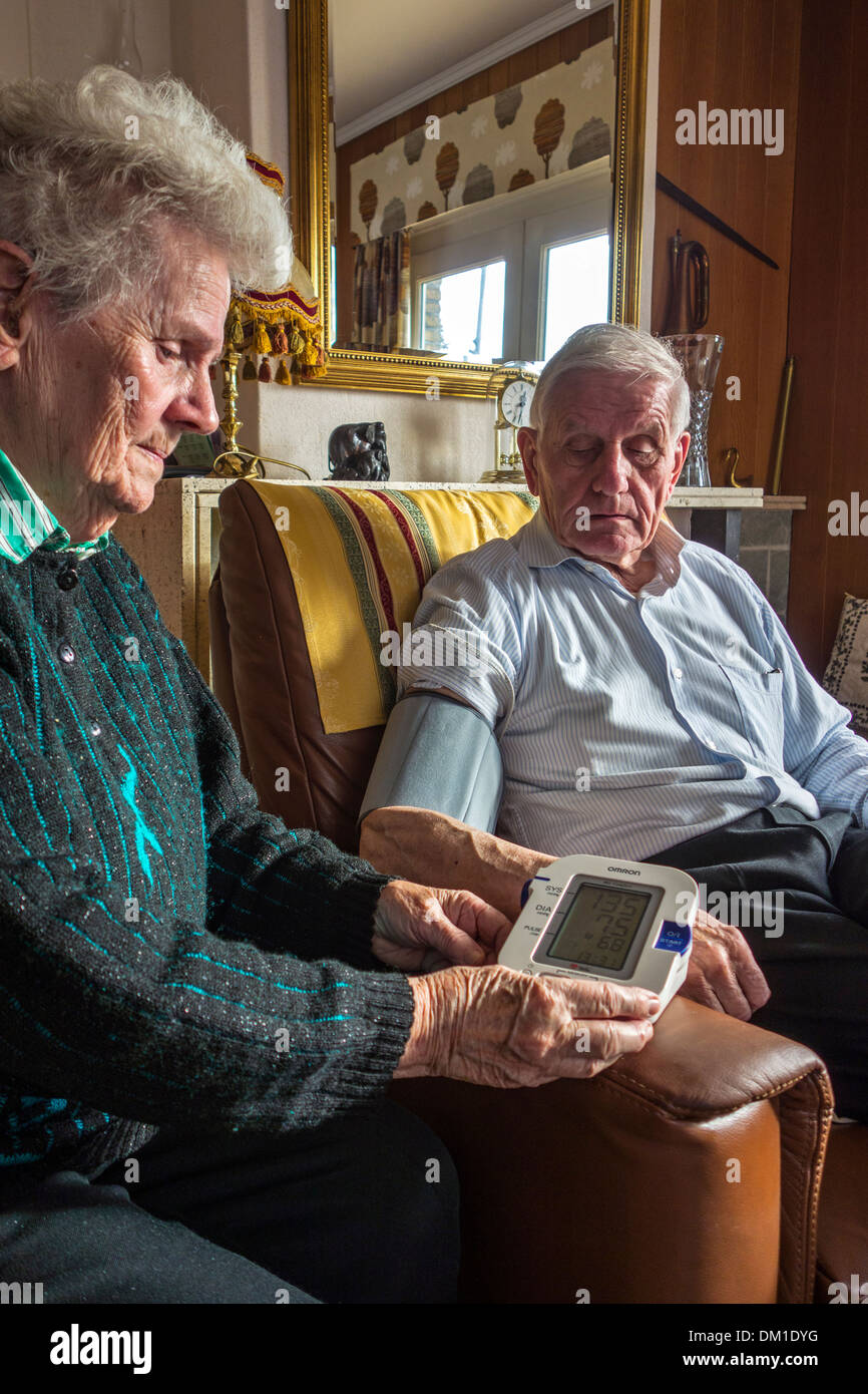 Close up of elderly couple checking their own blood-pressure using a digital blood pressure monitor in living room at home - Stock Image