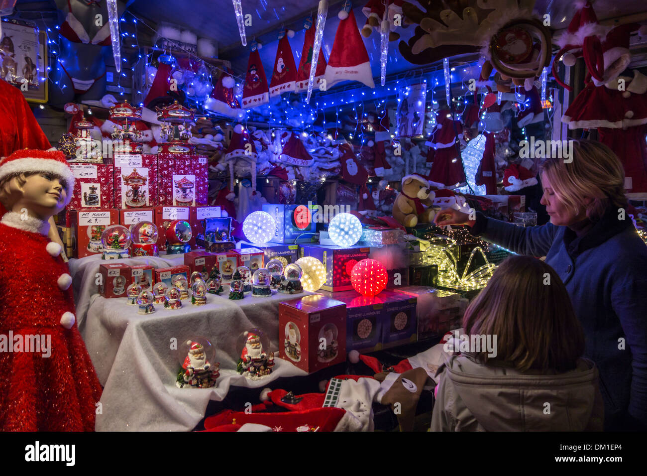 Mother and daughter buying Xmas decorations in market stall at evening Christmas market in winter - Stock Image