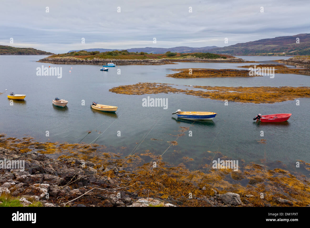 Small boats with outboard motors, moored near the Ulva ferry landing on Mull, Inner Hebrides, Scotland. - Stock Image