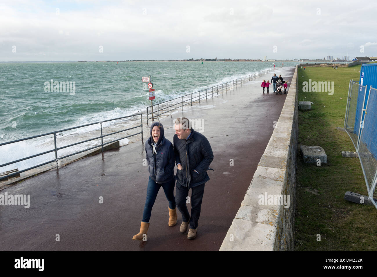 Walking on the seafront next to stormy seas, Southsea, Hampshire, UK - Stock Image