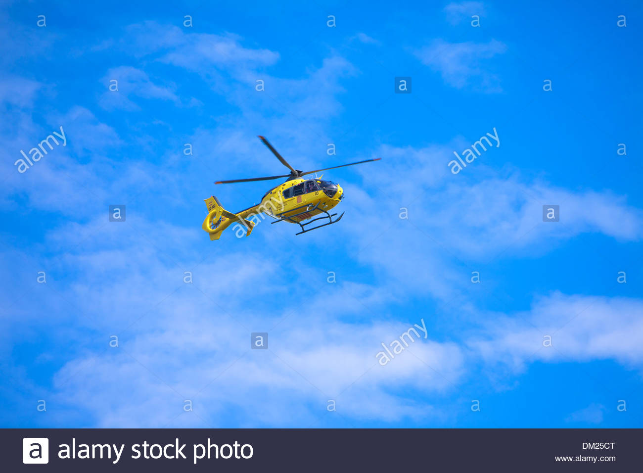 Yellow Catalonian Department of the Interior Helicopter with pilot flying overhead near Girona, Catalonia, Spain - Stock Image