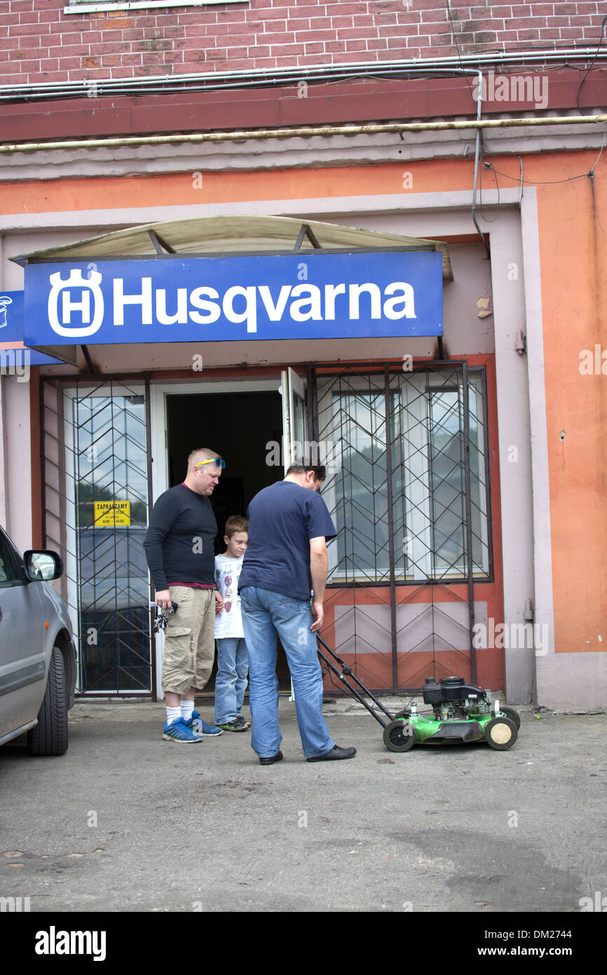 Customers picking up repaired lawnmower at the Husqvarna shop. Tomaszow Mazowiecki Central Poland Stock Photo