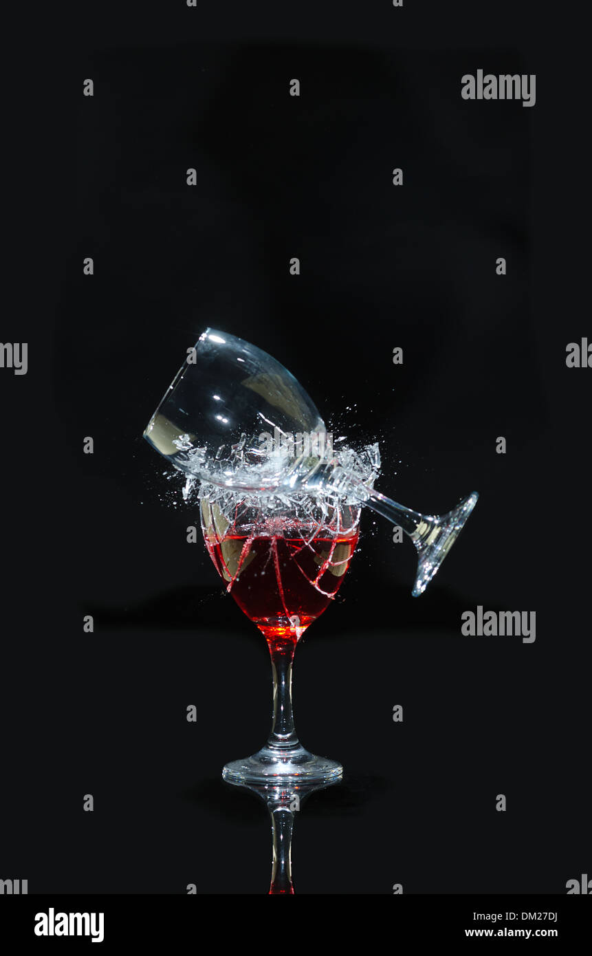 Smashing wine glasses on a reflective dark black background broken glass fragments flying as fracture lines spread through - Stock Image