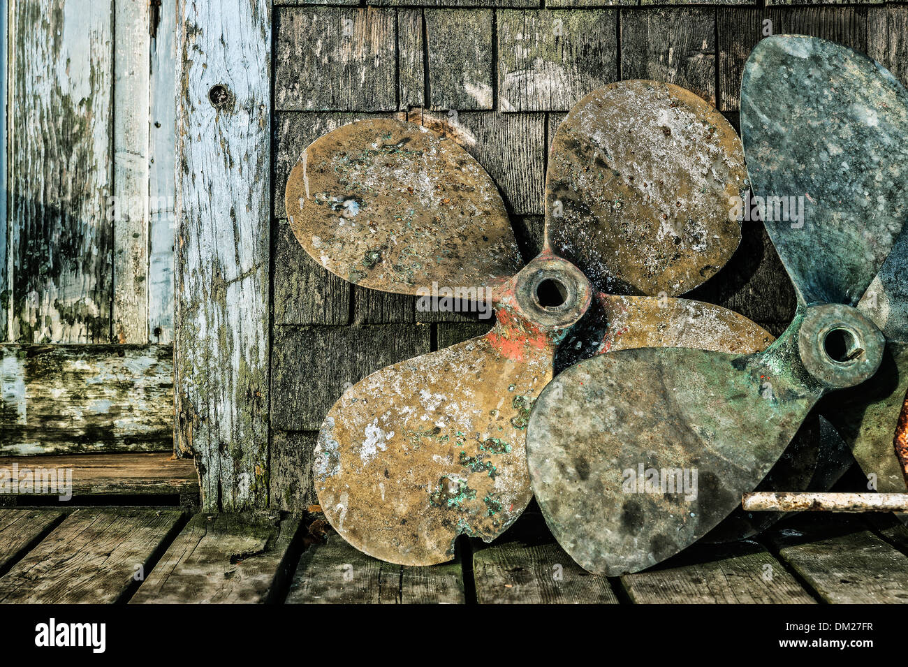Old boat propellers on a fishing village dock. - Stock Image