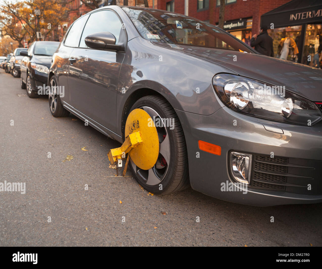A yellow wheel lock is attached this car's tire to prevent theft. Stock Photo