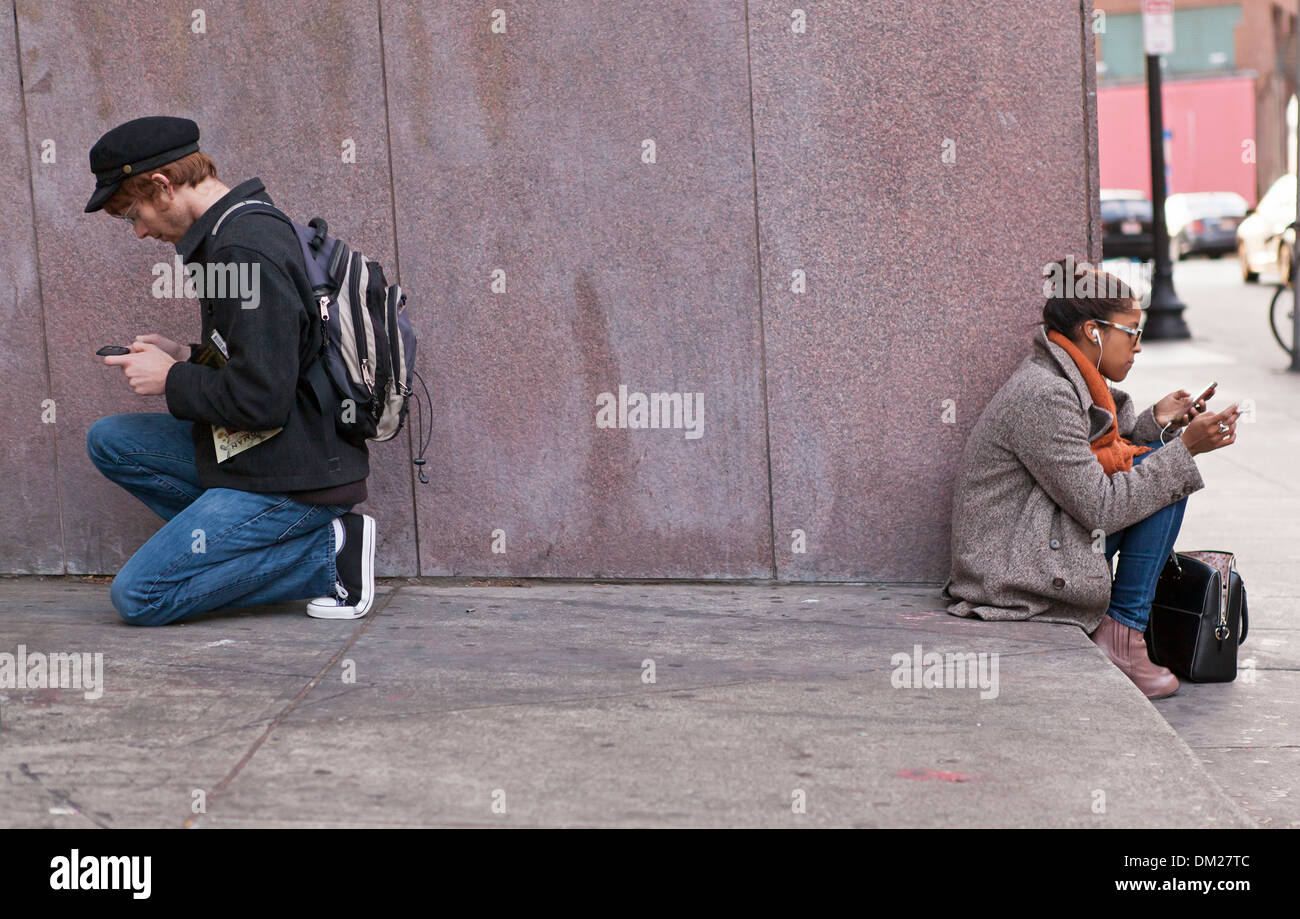 A man and woman are back to back as they stare at their mobile devices in Boston. - Stock Image