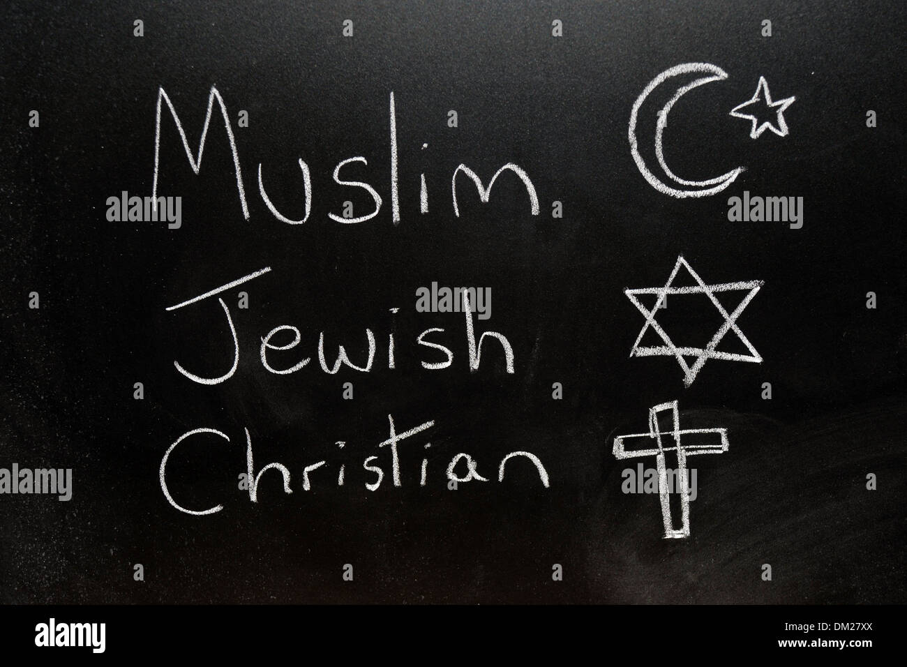 Close up of a blackboard with Muslim, Jewish and Christian written on it in chalk. - Stock Image