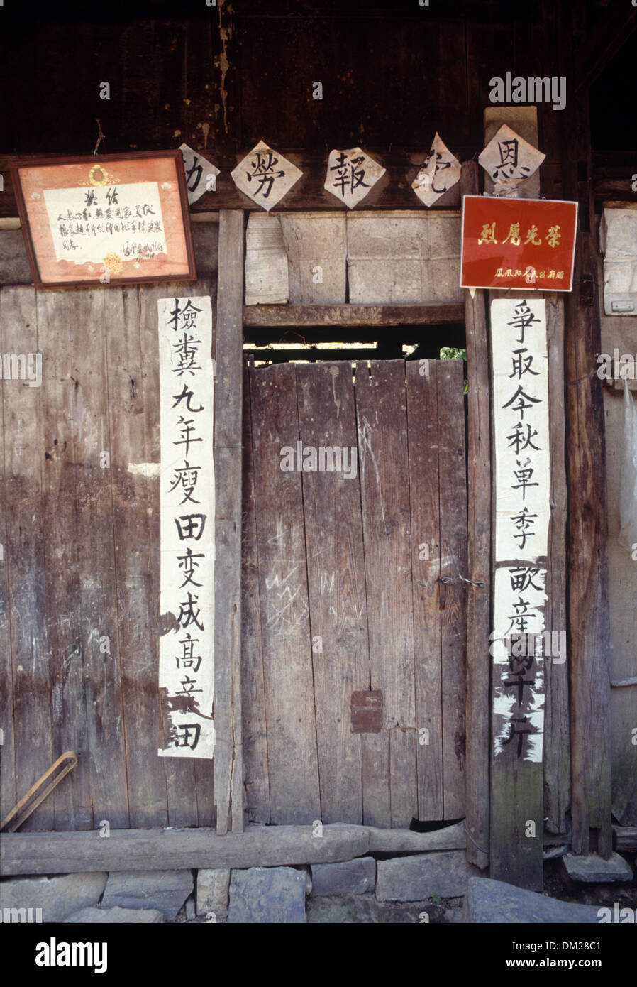 The door of a poor farm house with wordings praising the power of physical labour in Hunan Province, China - Stock Image