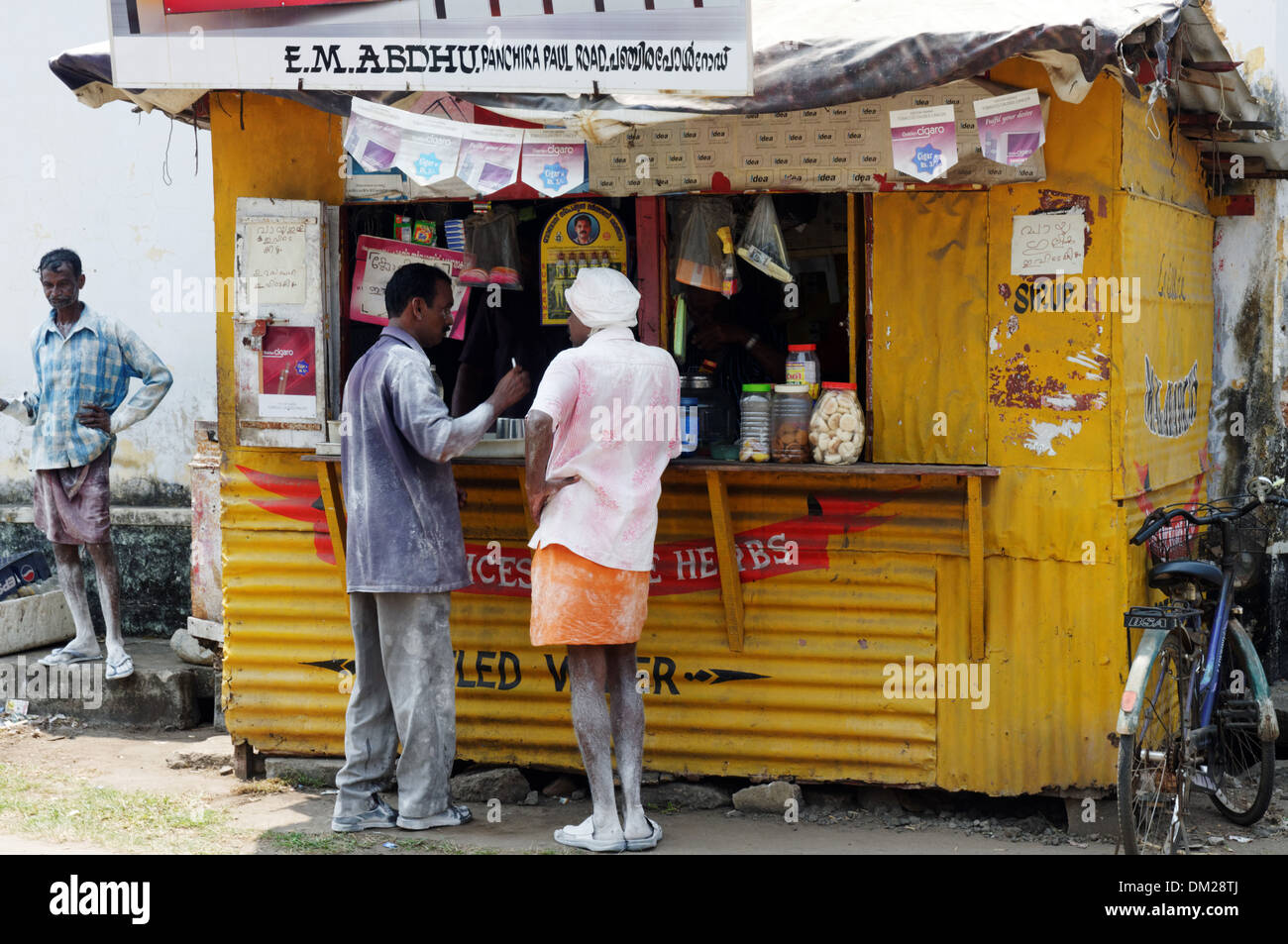 Indian workers buying sweets from a fast food kiosk in Kochin India - Stock Image