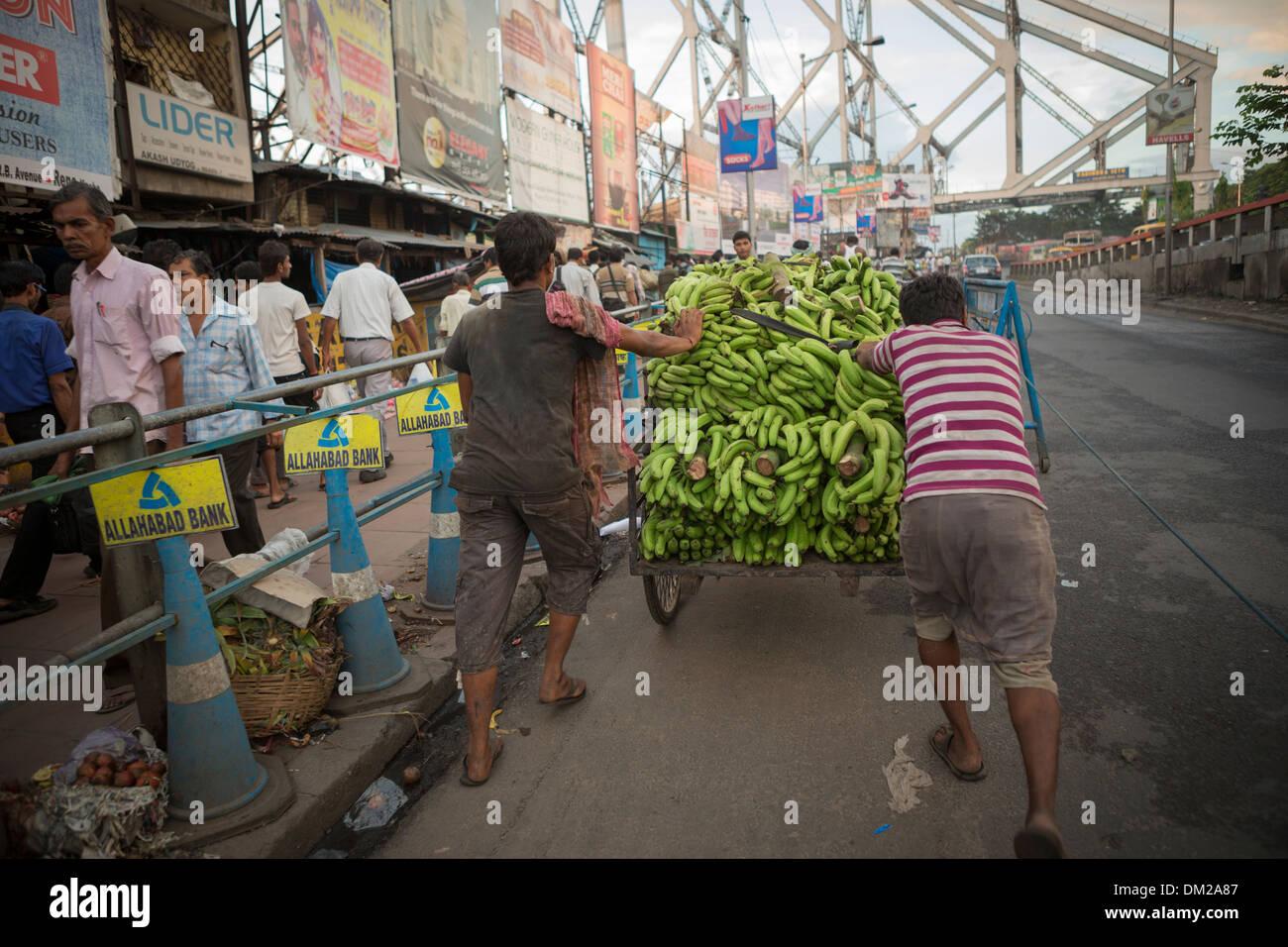 Street cart full of bananas crossing the Howrah Bridge in Calcutta (Kolkata), India - Stock Image