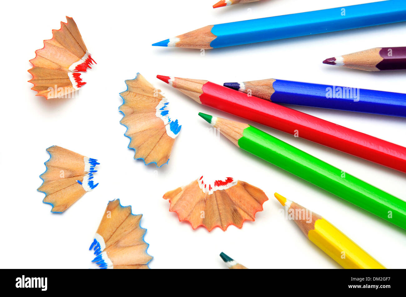 some colored pencils of different colors and pencil shavings on a white background - Stock Image