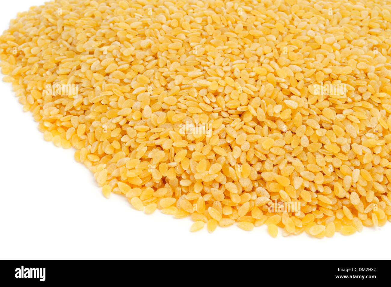 a pile of uncooked pastina, a variety of tiny pieces of pasta used in broth soups, on a white background - Stock Image