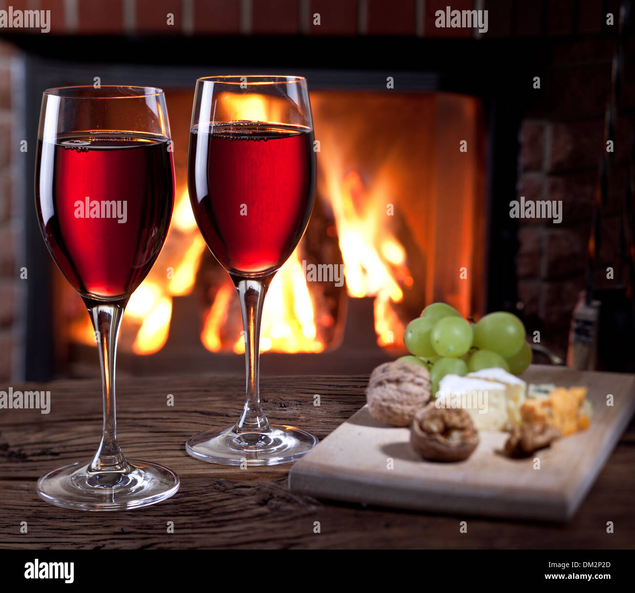 Romantic still life near the fireplace. Glasses of wine, cheese and nuts. - Stock Image