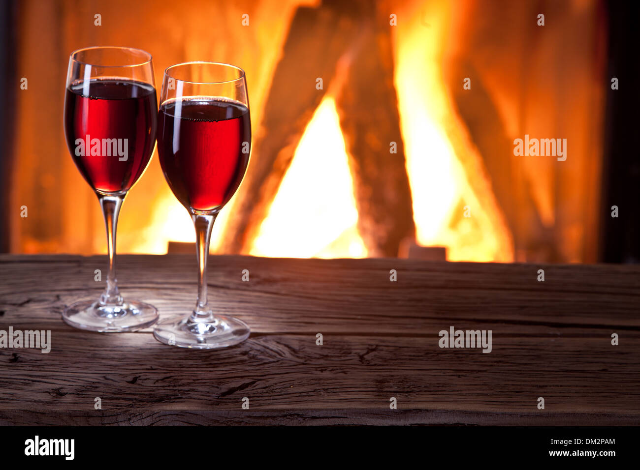 Glasses of wine and a fireplace fire. - Stock Image