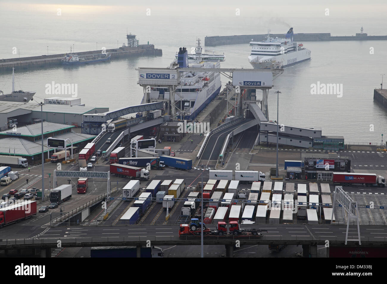 Ferries dock at the port of Dover, Kent, UK. Lorries are shown leaving one ferry as another maneuvers in the harbour Stock Photo