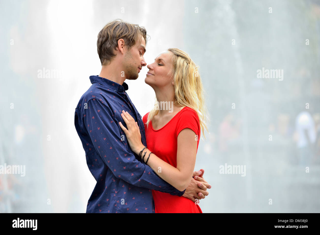 America United States USA East Coast New York Manhattan couple embrace kiss romance romantic love red dress blonde guy city man - Stock Image