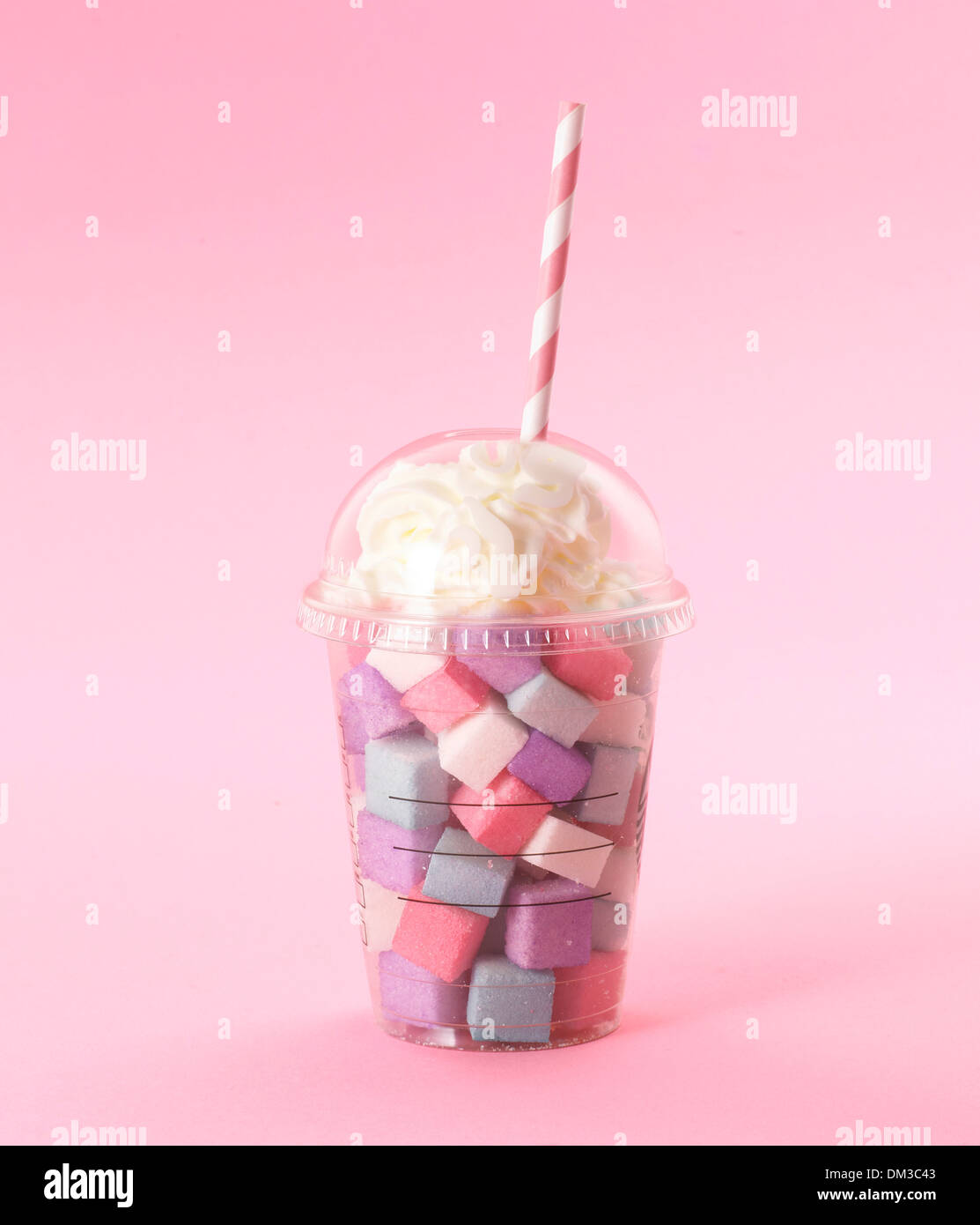 Multi coloured sugar milkshake style with straw cut out on pink background - Stock Image