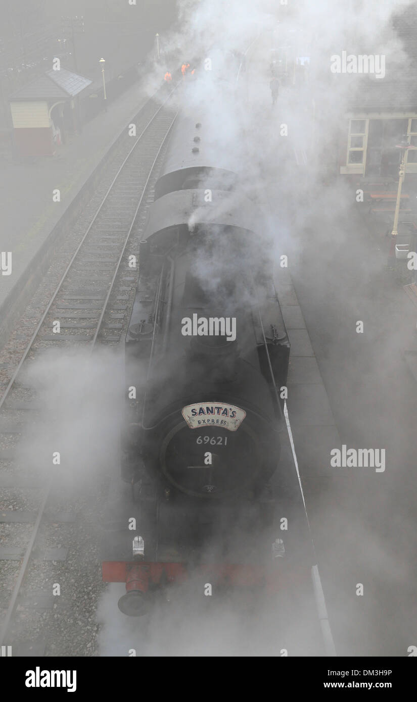 Froghall, Staffordshire, UK. 11th Dec, 2013. Surounded by thick fog and adding steam into the pea-souper, The Santa Express waits for a good view of the tracks ahead as it prepares to leave Froghall Station, on the Churnet Valley Railway, Staffordshire. Credit:  Joanne Roberts/Alamy Live News - Stock Image