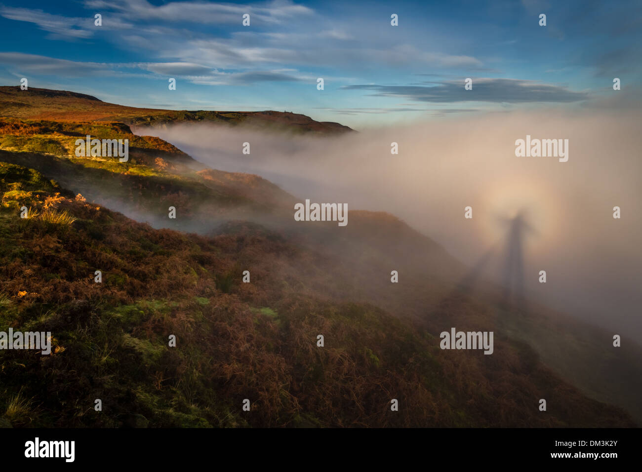 Dramatic brocken spectre of a person and dog on rural Ilkley Moor, Yorkshire, Wharfedale  UK - Stock Image