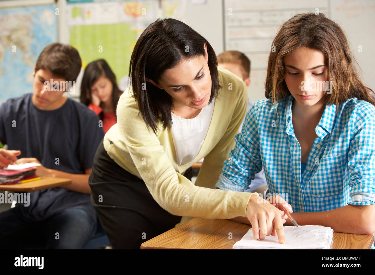 Teacher Helping Female Pupil Studying At Desk In Classroom - Stock Image