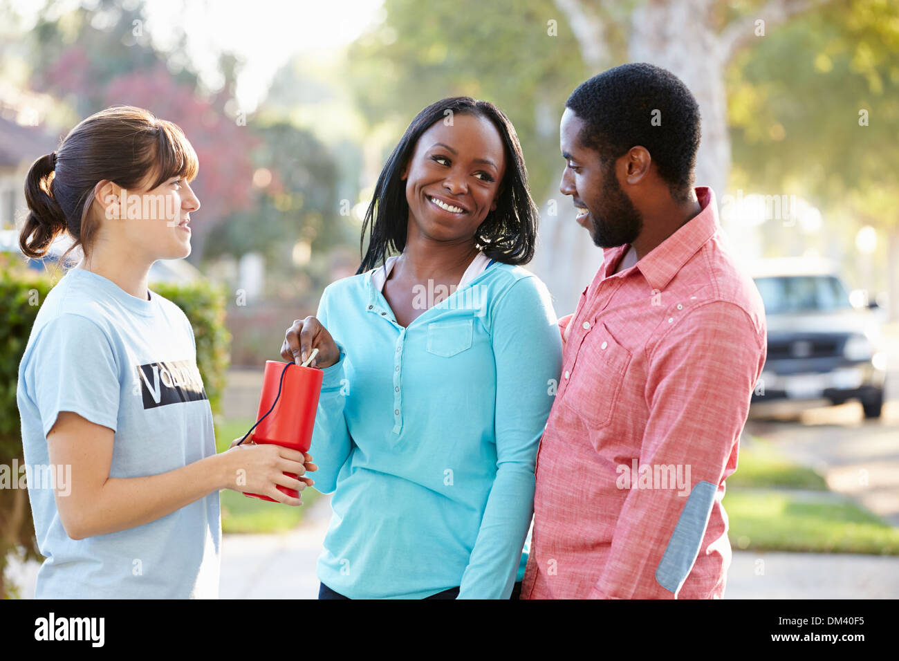 Charity Worker Collecting Sponsorship From Couple In Street - Stock Image