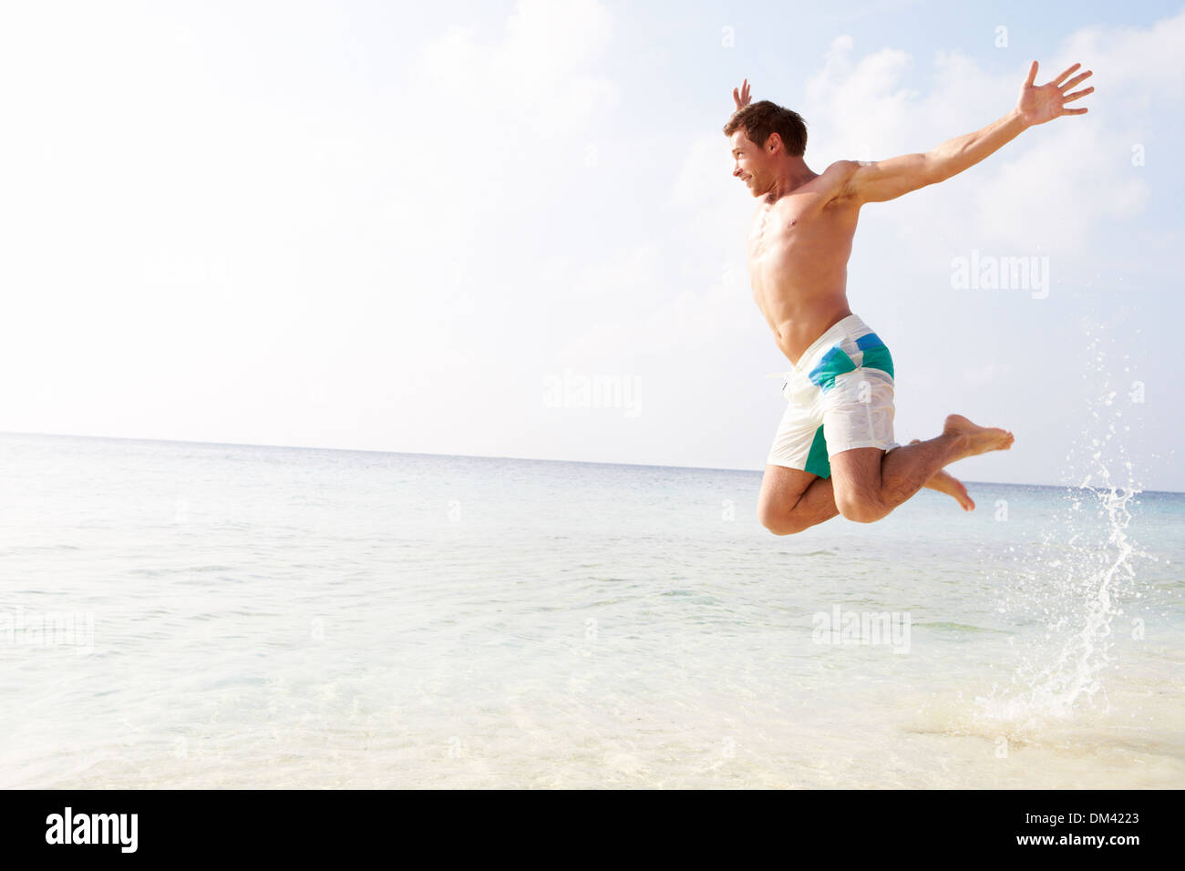 Man Jumping In The Air On Tropical Beach - Stock Image