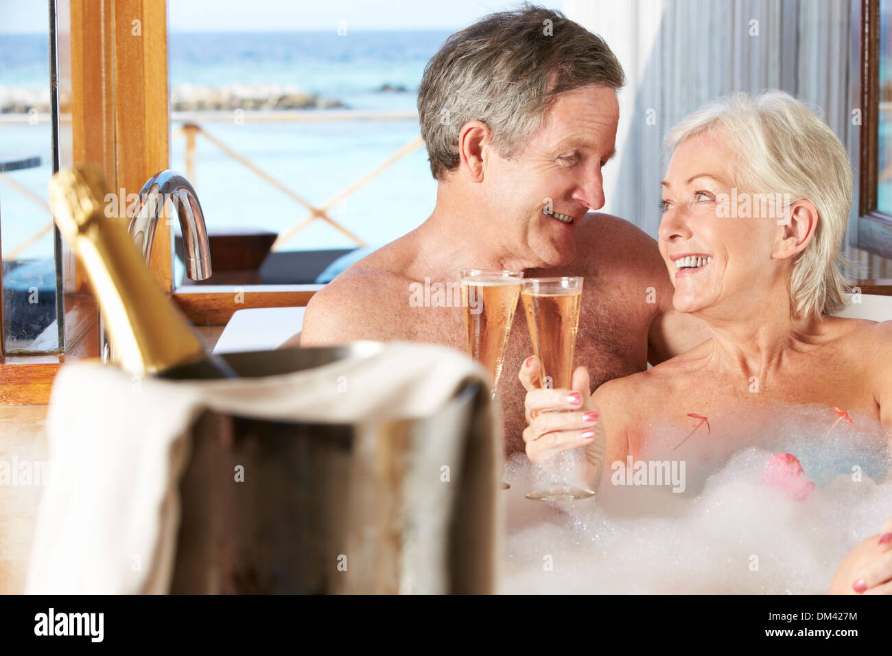 Senior Couple Relaxing In Bath Drinking Champagne Together - Stock Image