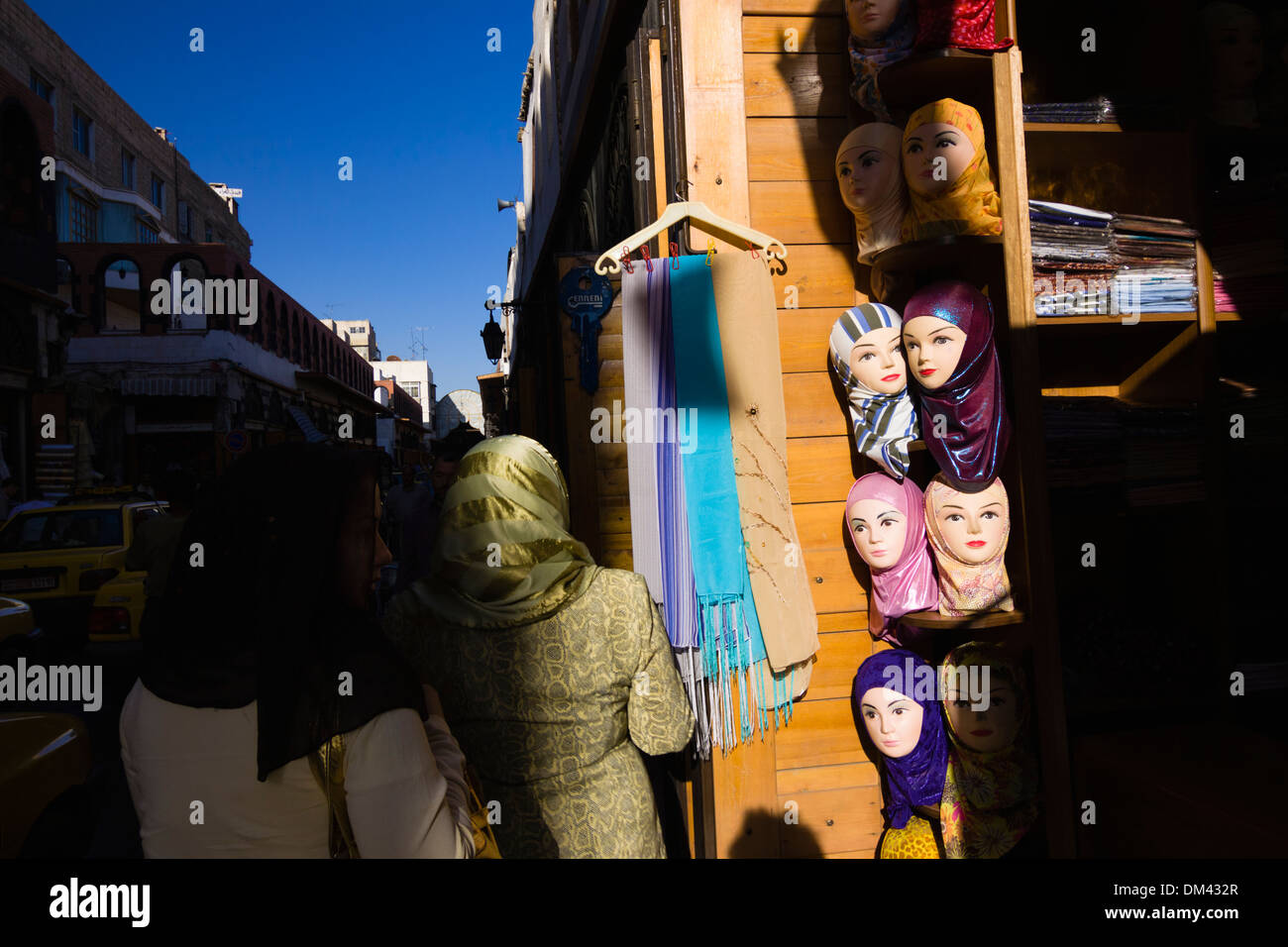 Arab women walk past a hijabs shop at the Via Recta street in Damascus, Syria Stock Photo