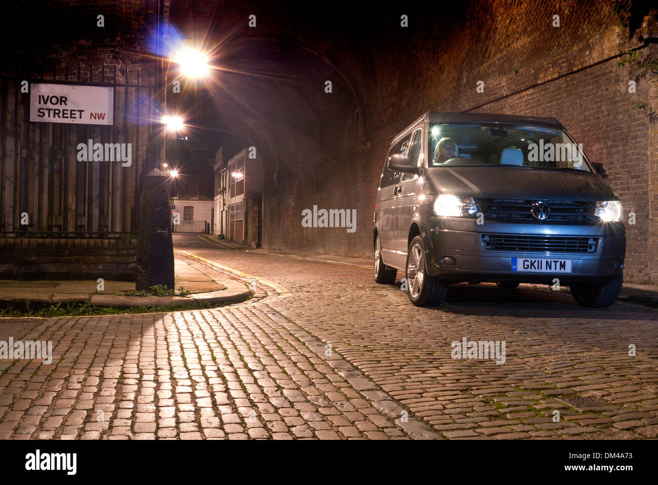 VW camper van driving on a London street at night - Stock Image