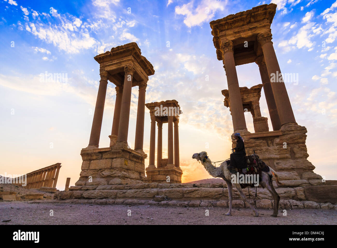 Man on camel at sunset beside the Tetrapylon of the ruins at Palmyra, Syria - Stock Image