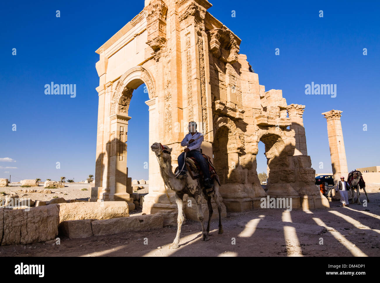 Man on camel beside the monumental arch of the ruins at Palmyra, Syria - Stock Image