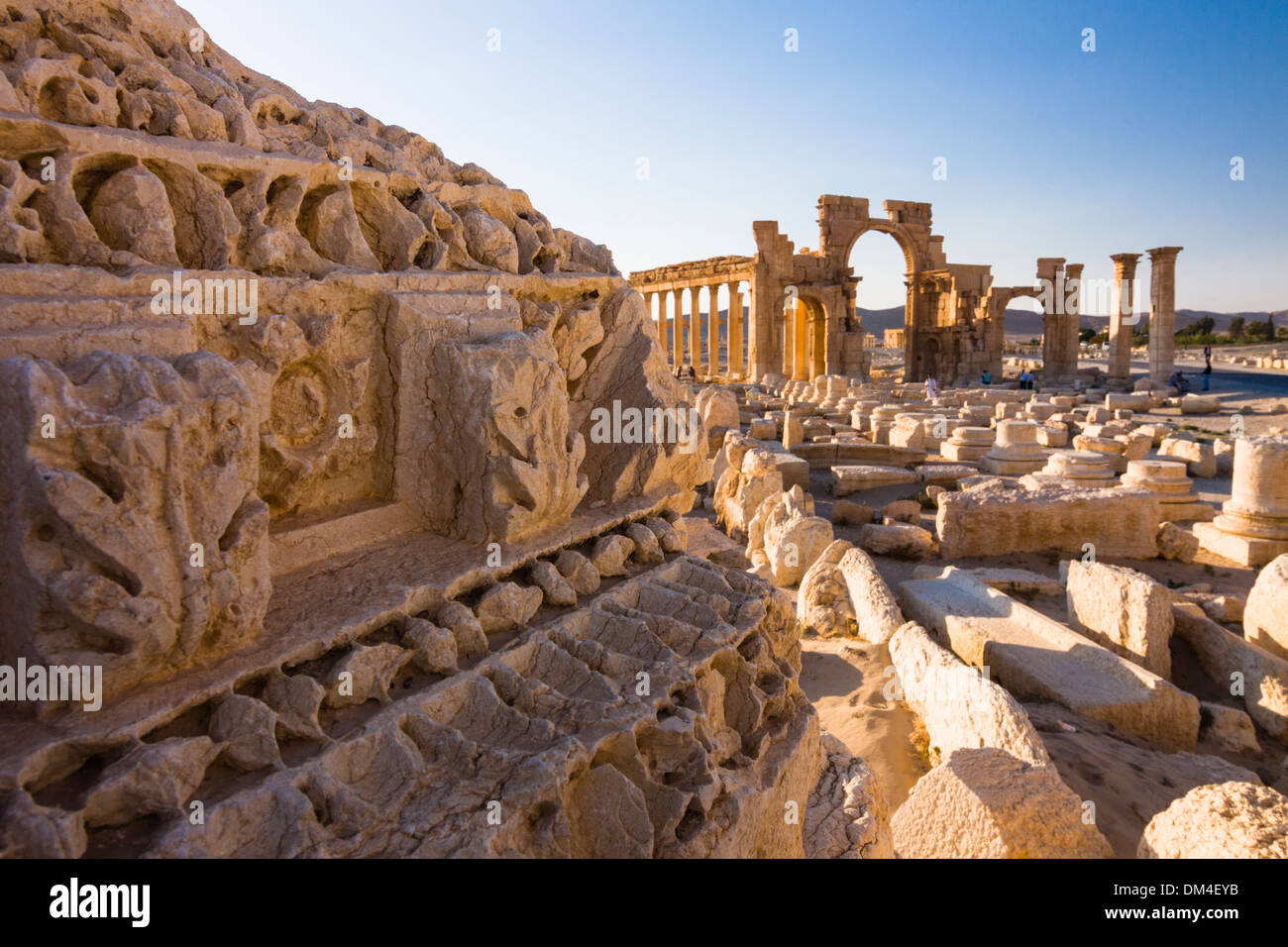 Architectural details with monumental arch in background at the ruins at Palmyra, Syria - Stock Image