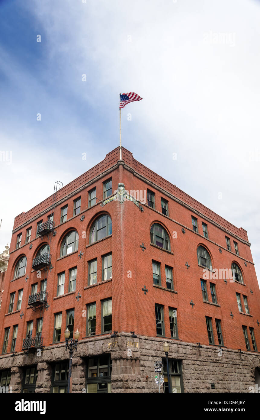 Historic red brick building in downtown Portland, Oregon with the American flag waving high above it - Stock Image