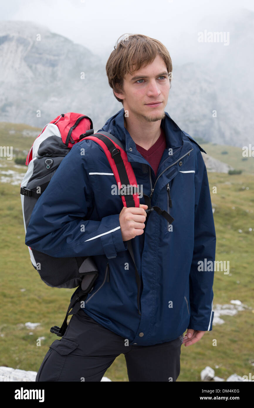 A young man is hiking in the mountains with a backpack - Stock Image