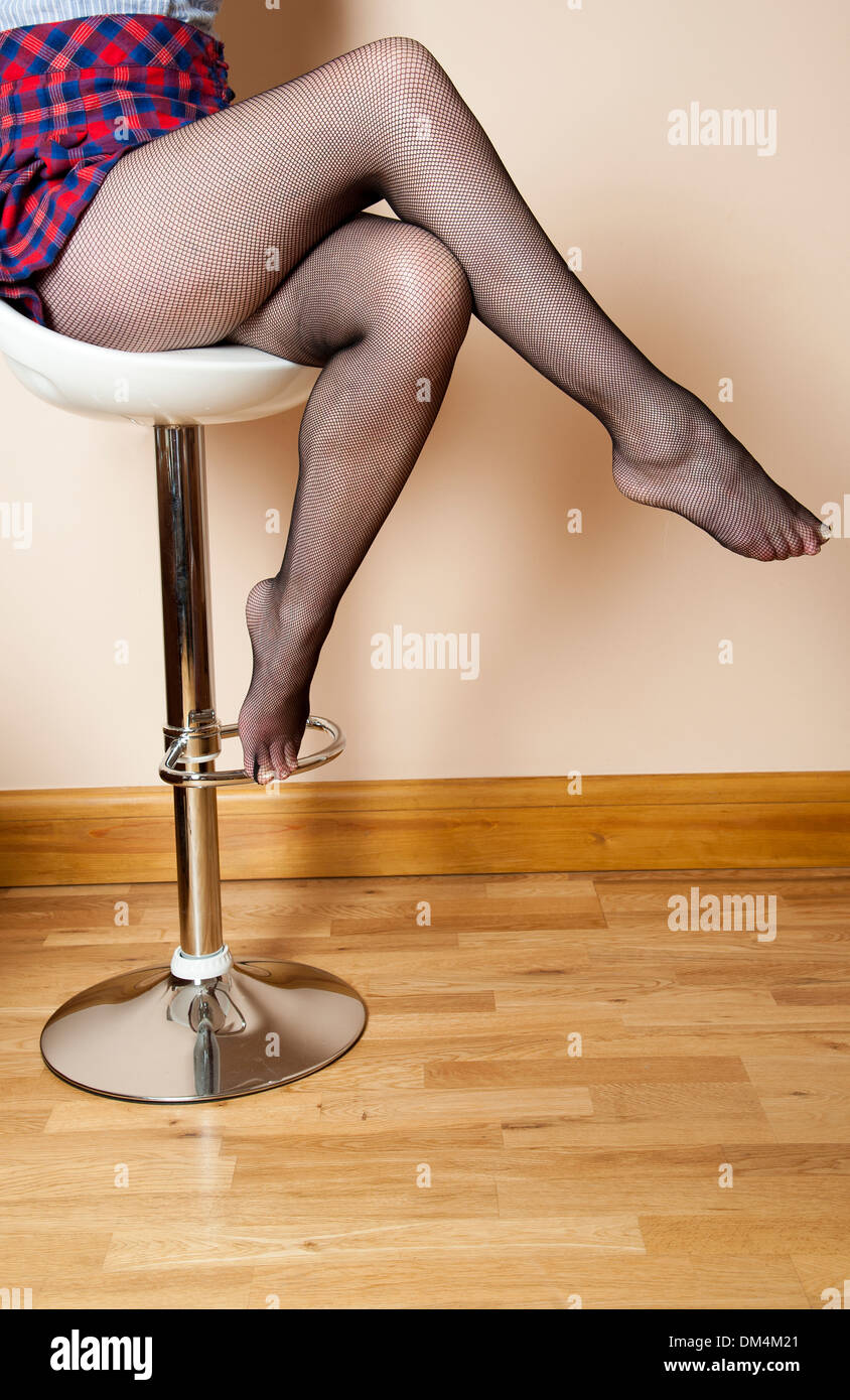 42ae9bcb2710 Woman sitting on a high stool wearing black fishnet tights - Stock Image