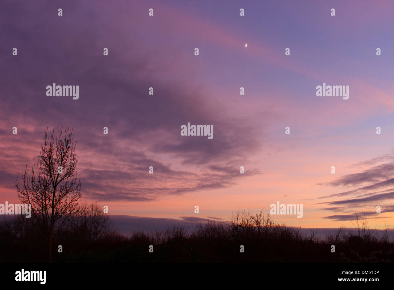 Epic sunset with different colours and some clouds in the sky. - Stock Image