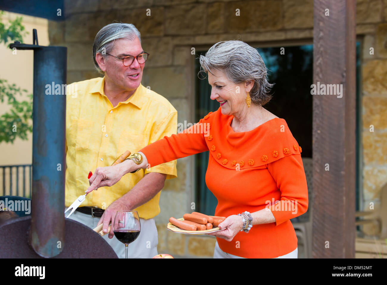 Mature couple preparing a barbecue in the back of their home, Texas, USA. Woman is putting sausages on the grill. - Stock Image