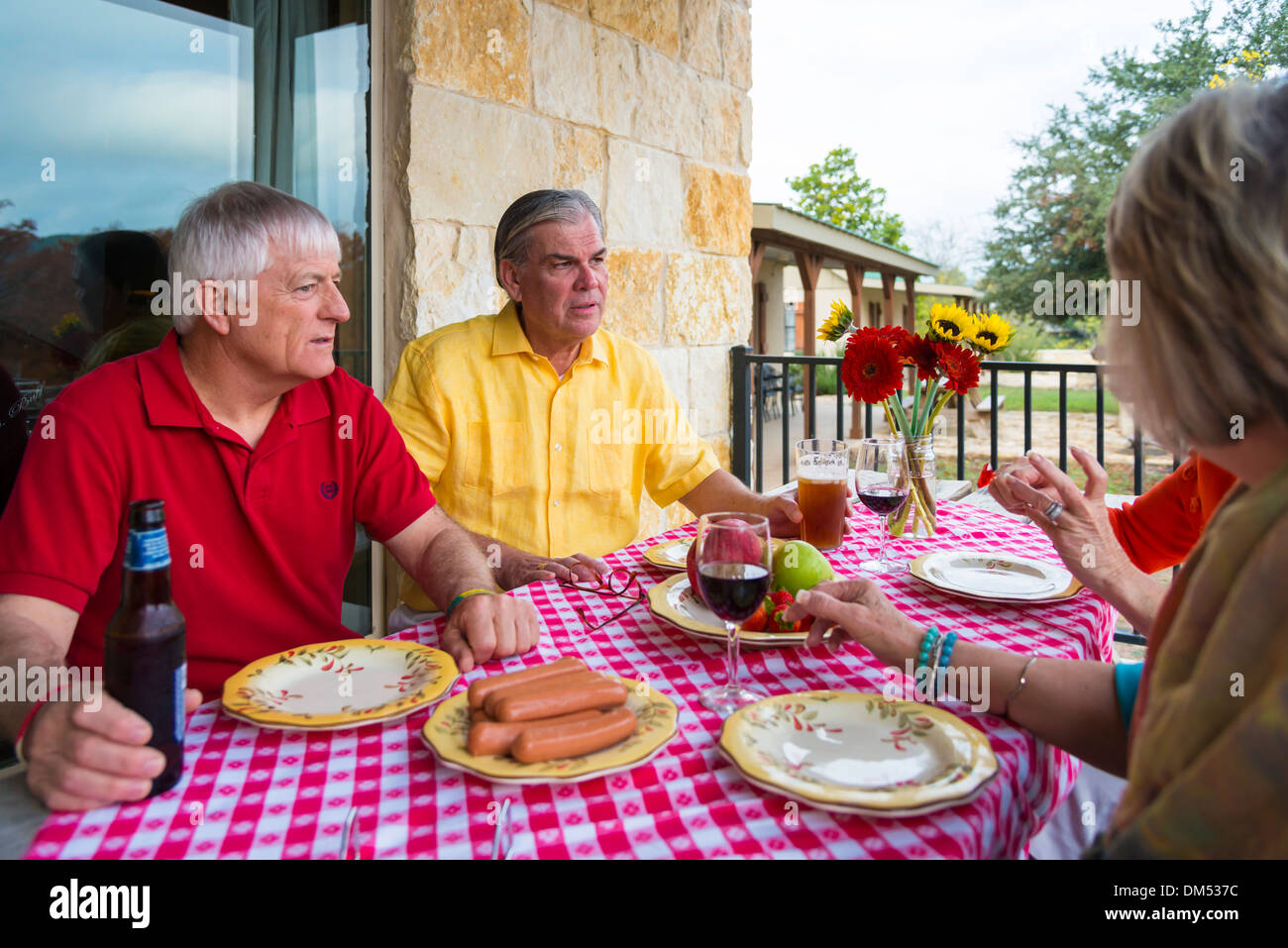 Two retired couples at a backyard barbecue party. Food and drinks, like fresh fruit, sausages, beer and wine, on the table. - Stock Image