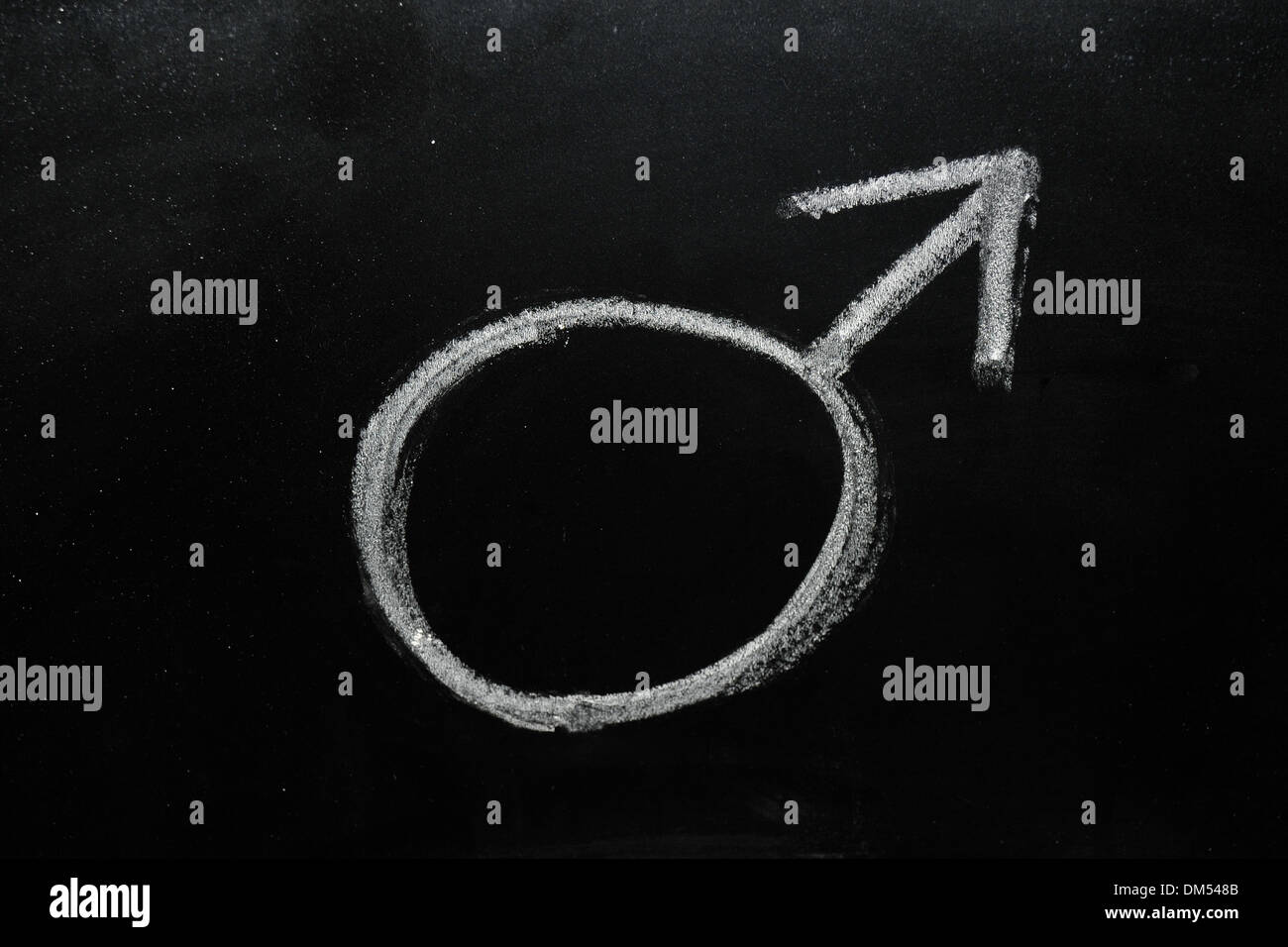 Male gender symbol drawn on a blackboard in chalk. - Stock Image
