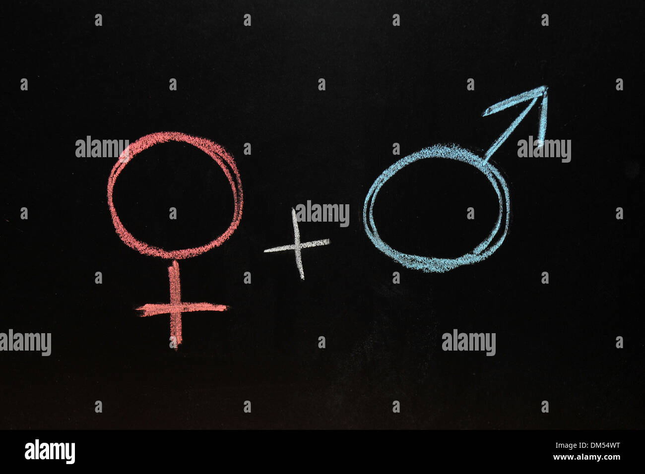 A male and a female gender symbols drawn on a blackboard in chalk. - Stock Image