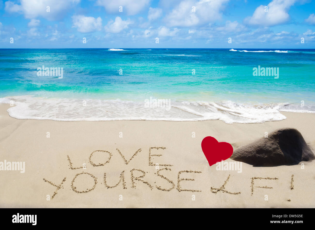 Sign 'Love yourself' with heart on the sandy beach by the ocean - Stock Image