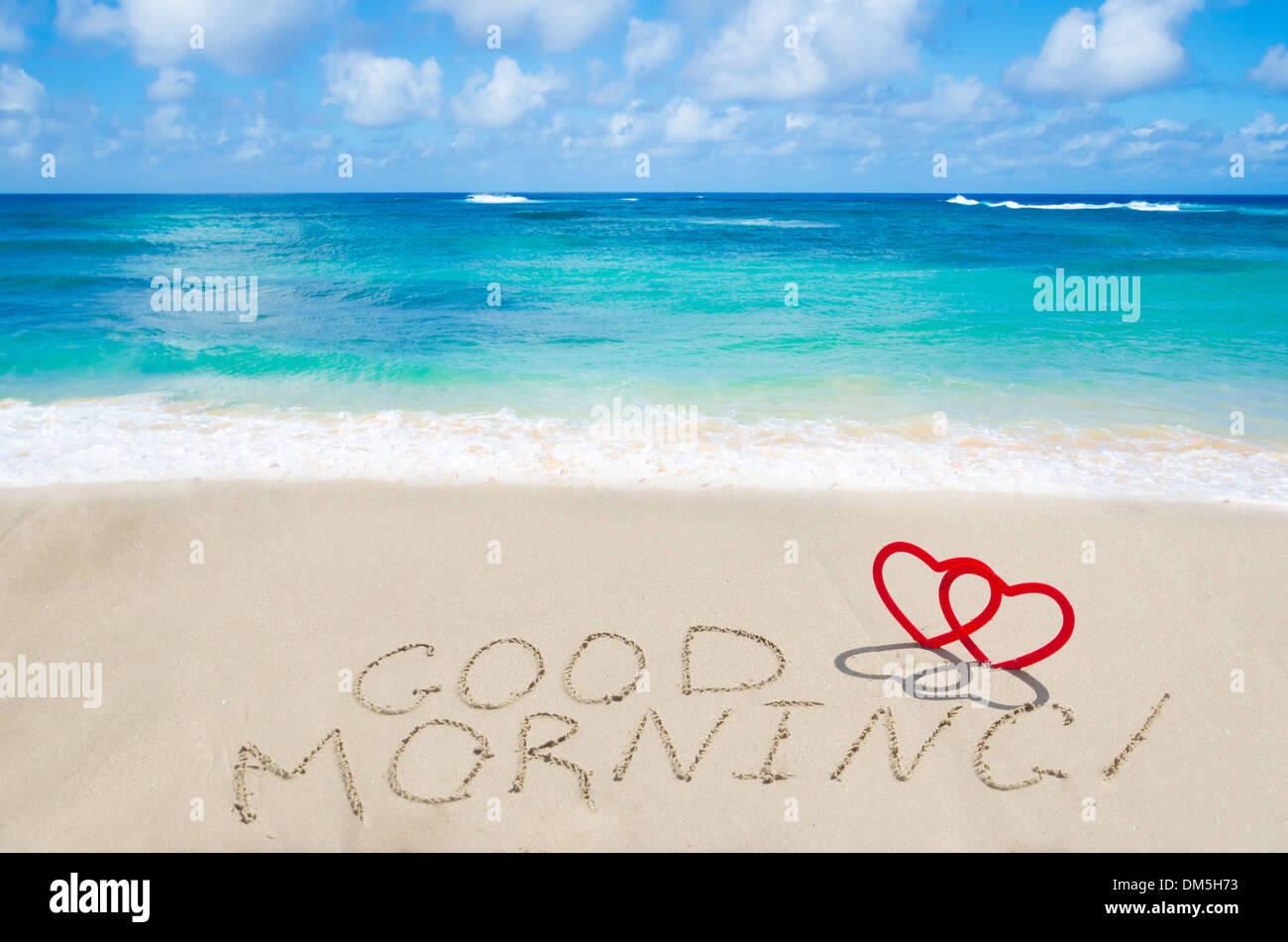 Sign 'Good morning' with two hearts on the sandy beach by the ocean - Stock Image